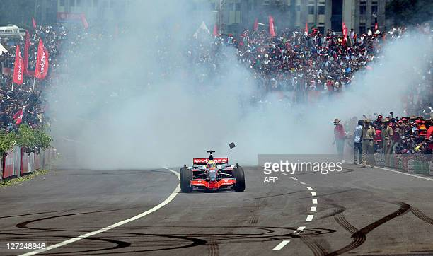 Formula One race car driver Lewis Hamilton burns rubber in his Vodafone McLaren Mercedes MP423 car on a special track created for the event on the...