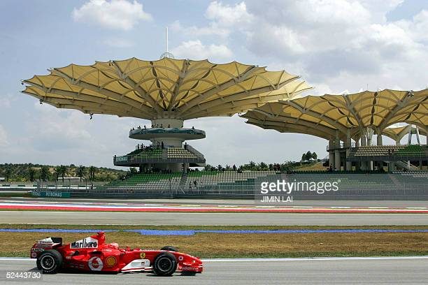 Formula One World Champion Michael Schumacher of Germany powers his Ferrari past the grandstand at the Sepang International Circuit 18 March 2005...