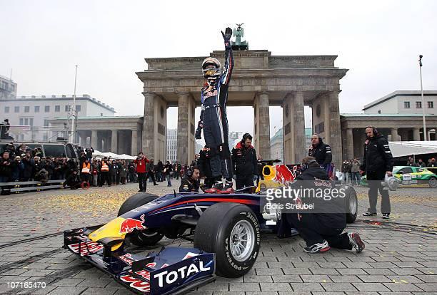Formula One world champion Sebastian Vettel celebrates during his visit at Brandenburg Gate on November 27 2010 in Berlin Germany