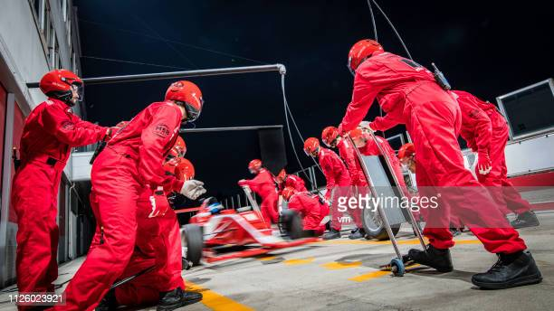 formula race car driving into the pit - pit stop stock pictures, royalty-free photos & images