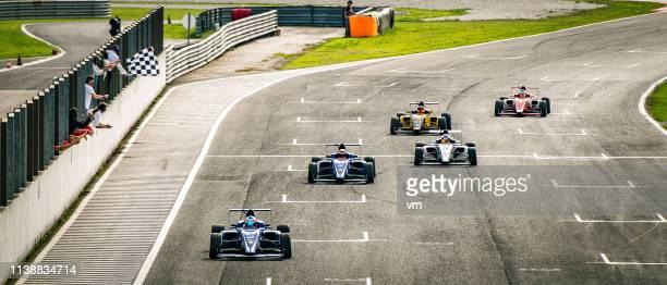 formula race auto's nadert de finishlijn - autosport stockfoto's en -beelden