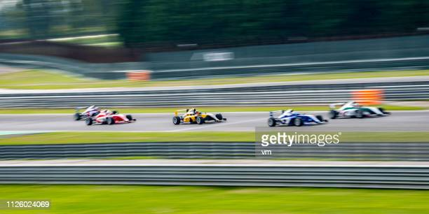 formula race cars driving fast - grand prix motor racing stock pictures, royalty-free photos & images