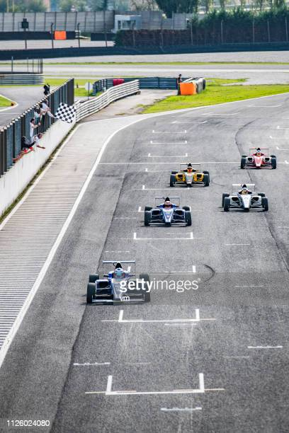 formula race cars on the home stretch - grand prix motor racing stock pictures, royalty-free photos & images