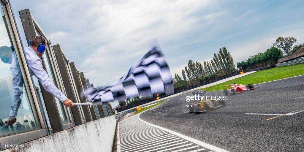 Formula race cars speeding towards the finish line : Stock Photo
