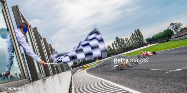 formula race cars speeding towards the finish line - pista sportiva foto e immagini stock