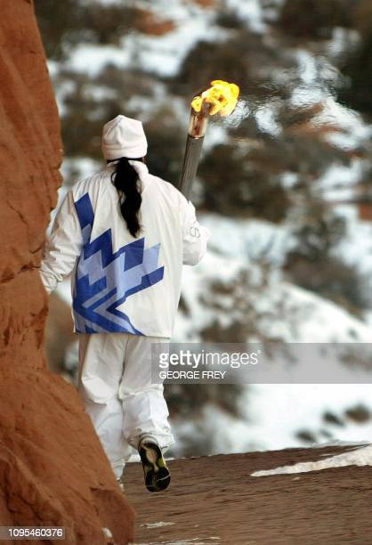 Forrest Cuch runs the Olympic torch down the trail from Delicate Arch in Arches National Park near Moab Utah 04 February 2002 The torch arrived in...