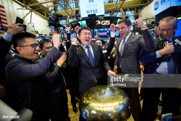 Forrest Li, chairman, chief executive officer and co-founder of Sea Ltd., center, rings a ceremonial bell during the company's initial public...
