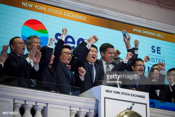 Forrest Li, chairman, chief executive officer and co-founder of Sea Ltd., center left, and Nick Nash, president of Sea Ltd., center right, ring the...