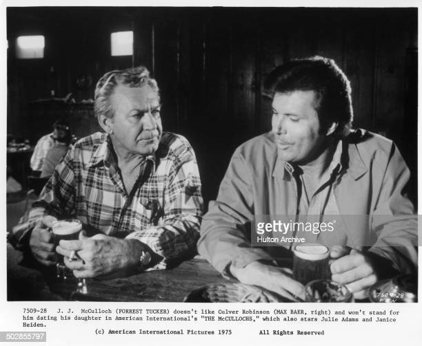 """Forrest Tucker and Max Baer Jr. Have a drink in a scene for the movie """"The Wild McCullochs"""" circa 1975."""