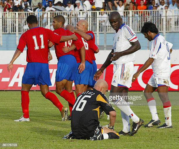 Costa Rica midfielder Danny Fonseca is congratulated by is teammates after scoring a goal as French goalkeeper Fabien Barthez speaks with his...
