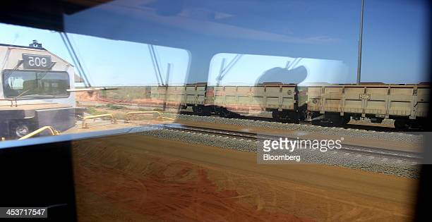 A Fortescue Metals Group Ltd train loaded with iron ore is seen through the window of another train as it travels across the Pilbara region towards...
