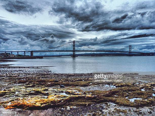 Forth Road Bridge Over River Against Cloudy Sky