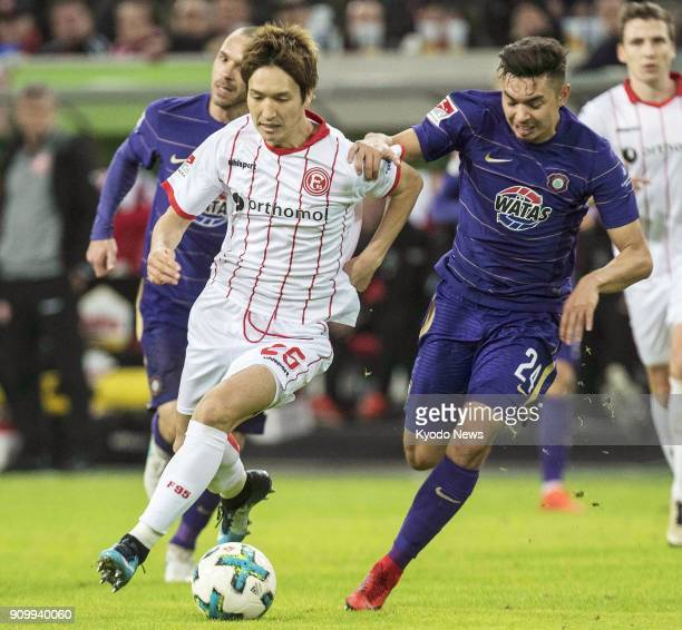 Fortuna Dusseldorf's Genki Haraguchi and Erzgebirge Aue's JohnPatrick Strauss vie for the ball during the second half of Dusseldorf's 21 win at home...