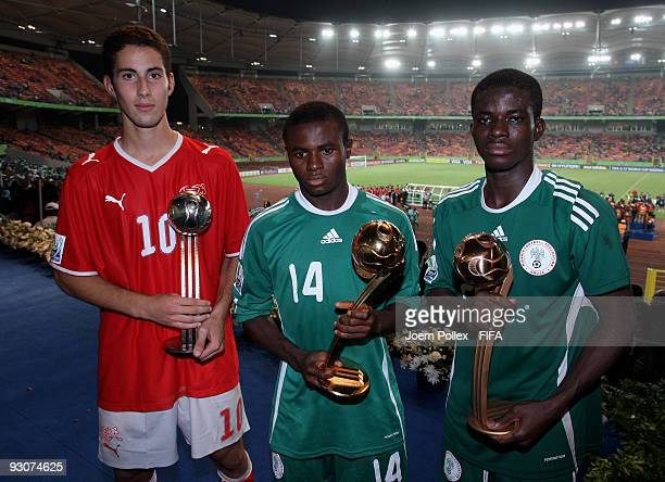 ABUJA NIGERIA NOVEMBER 15 Fortune Chukwudi and Sani Emmanuel of Nigeria and Nassim Ben Khalifa of Switzerland pose with the Ball Trophies after the...