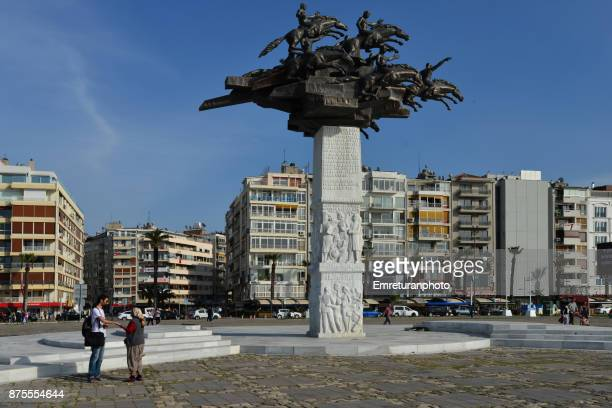 a fortune teller and a man talks in front of the republic tree monument at gundogdu square in izmir on a sunny day. - emreturanphoto stock pictures, royalty-free photos & images