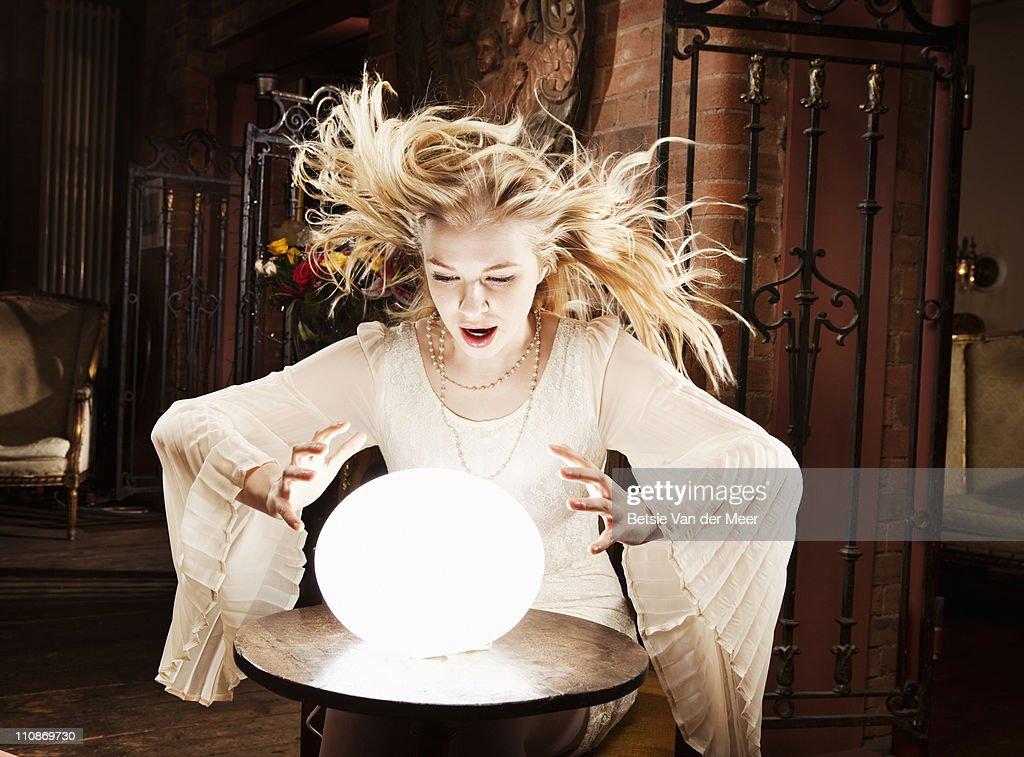 Fortune teller gazes in crystal ball. : Stock Photo
