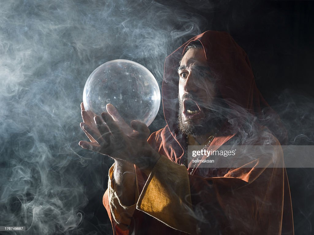 Fortune teller in fantastical costume holding crystal ball : Stock Photo