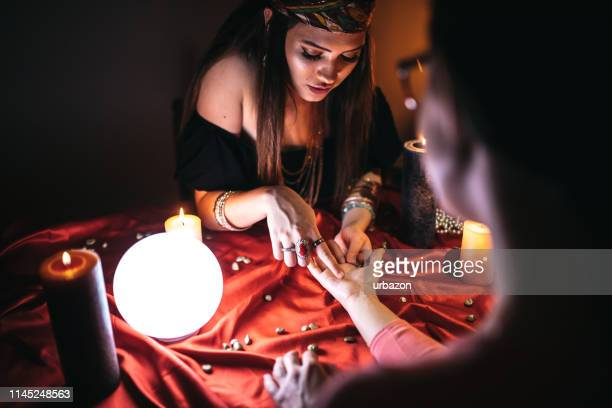 fortune teller reading from palm - fate stock photos and pictures