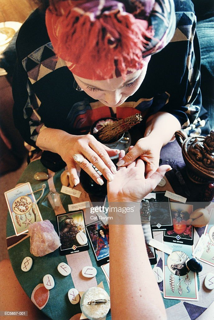 Fortune teller reading palm, overhead view : Stockfoto