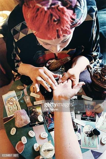Fortune teller reading palm, overhead view
