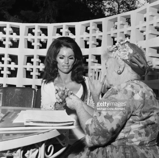 Fortune teller reading the palms of an unspecified female guest attending a party held at the Beverly Hills Hotel on Sunset Boulevard in Beverly...