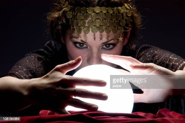 fortune teller with glowing crystal ball - gypsy stock pictures, royalty-free photos & images