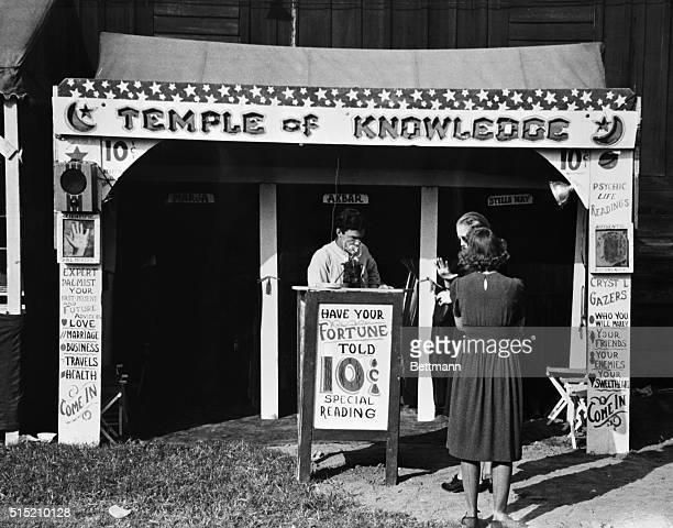 Fortune teller's booth showing advertising posters admission taker and two women customers waiting their turns Undated photograph BPA2# 2930