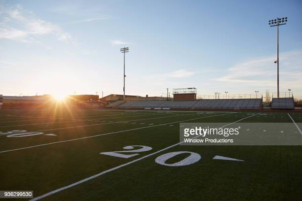 forty yard line on green playing field at sunset - forty yard line stock pictures, royalty-free photos & images