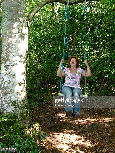 Forty year old woman playing on swing hanging from a tree UK