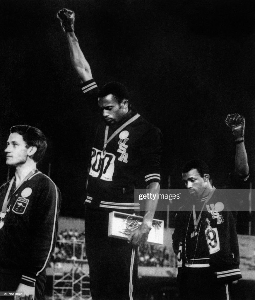 'Forty years after Tommie Smith and John Carlos raised their fists in a civil rights gesture on the Olympic medal stand in Mexico City, protests on the podium could make a comeback in Beijing.'. (FILES) US athletes Tommie Smith (C) and John Carlos (R) raise their gloved fists in the Black Power salute to express their opposition to racism in the USA during the US national anthem, after receiving their medals 17 October 1968 for first and third place in the men's 200m event at the Mexico Olympic Games. At left is Peter Norman of Australia who took second place.