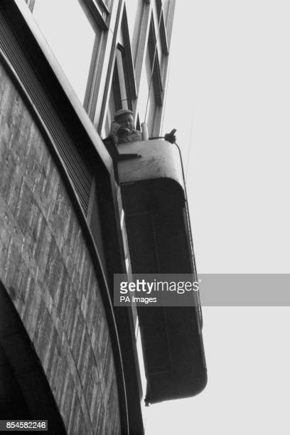 Fortyoneyear old Charlie O'Brien one of the two window cleaners speaks on the telephone which is carried on the cleaning cradle on the Post Office...