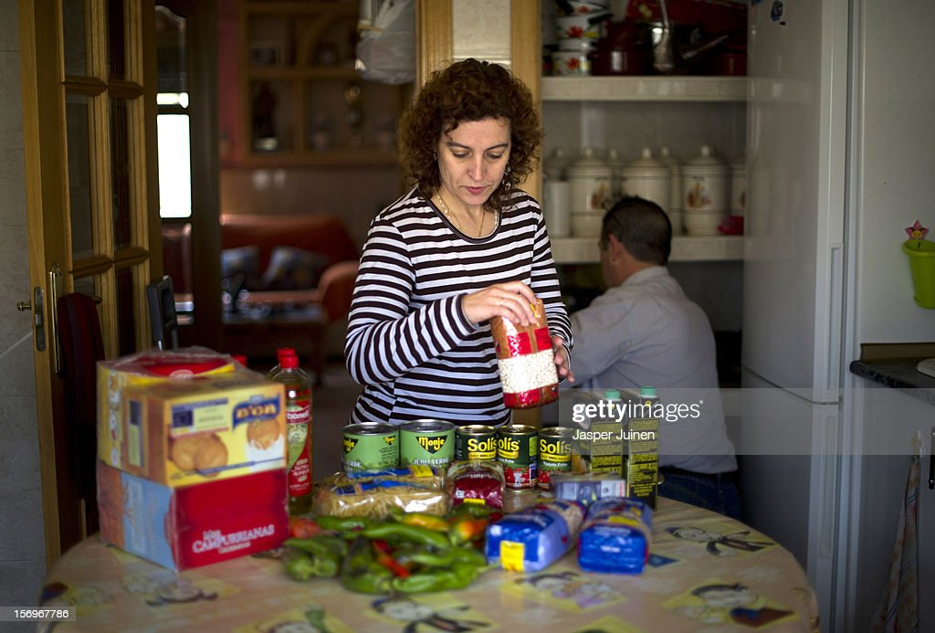 Forty-year old Maria Regine Bueno Villar (L) and her husband, forty-eight year old former door factory worker, Angel Perez Fernandez store food they received at a Red Cross point in their kitchens closet on November 23, 2012 in Villacanas, Spain. During the boom years, where in its peak Spain built some 800,000 houses a year accompanied by the manufacturing of millions of wooden doors where needed, the people of Villacanas were part of Spain's middle class enjoying high wages and permanent jobs. During the construction boom years the majority of the doors used within these new developments were made in this small industrial town. Approximately seven million doors a year were once assembled here and the factory employed a workforce of almost 5700 people, but the town is now left almost desolate with the Villacanas industrial park now empty and redundant. With Spain in the grip of recession and the housing bubble burst, Villacanas is typical of many former buoyant industrial Spanish towns now struggling with huge unemployment problems.