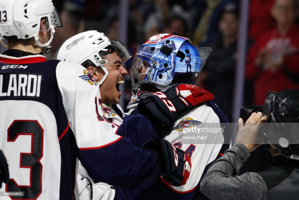 Forward Adam Laishram #19 of the Windsor Spitfires celebrates the 7-1 win against the Seattle Thunderbirds with goaltender Michael DiPietro #64 on May 21, 2017 during Game 3 of the Mastercard Memorial Cup at the WFCU Centre in Windsor, Ontario, Canada.