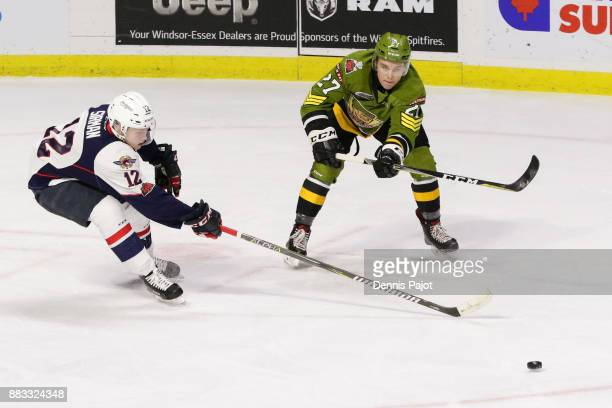 Forward Adam McMaster of the North Bay Battalion moves the puck against forward William Sirman of the Windsor Spitfires on November 30 2017 at the...