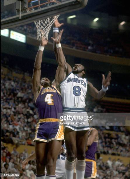 Forward Adrian Dantley of the Los Angeles Lakers battles forward Marvin Barnes of the Buffalo Braves for a rebound during a National Basketball...