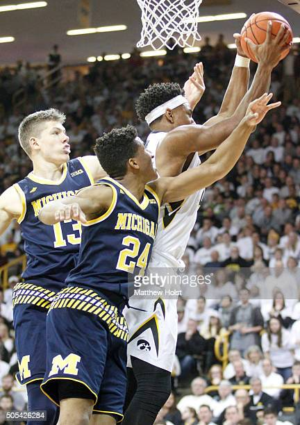 Forward Ahmad Wagner of the Iowa Hawkeyes grabs a rebound away from forward Moritz Wagner and guard Aubrey Dawkins of the Michigan Wolverines in the...