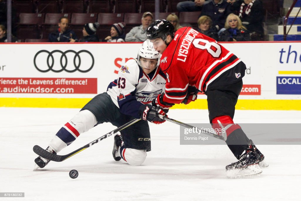 Forward Alan Lyszczarczyk #8 of the Owen Sound Attack moves the puck against defenceman Louka Henault #43 of the Windsor Spitfires on November 16, 2017 at the WFCU Centre in Windsor, Ontario, Canada.