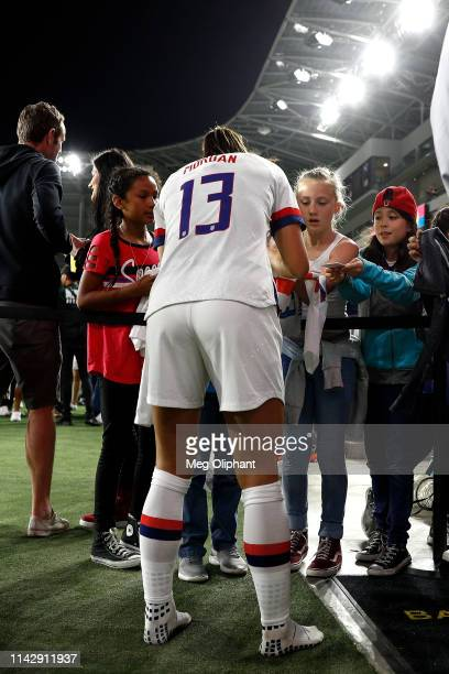 Forward Alex Morgan of the United States Women's National Team signs autographs on her way off the field after defeating Belgium at Banc of...