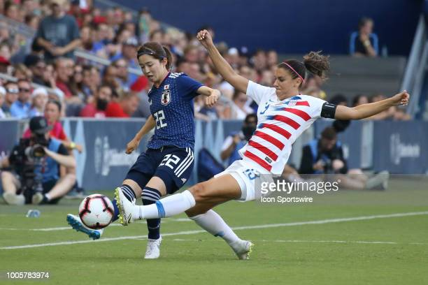 USA forward Alex Morgan slides in to defend against Japan defender Risa Shimizu in the first half of a women's soccer match between Japan and USA in...
