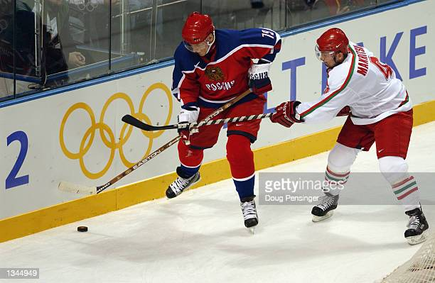Forward Alexei Yashin of Russia plays the puck while being pressured by defenseman Aleksandr Makritsky of Belarus during the Salt Lake City Winter...