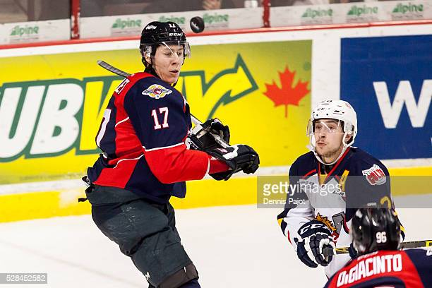 Forward Andrew Mangiapane of the Barrie Colts battles for the puck against defenceman Logan Stanley of the Windsor Spitfires on February 25, 2016 at...