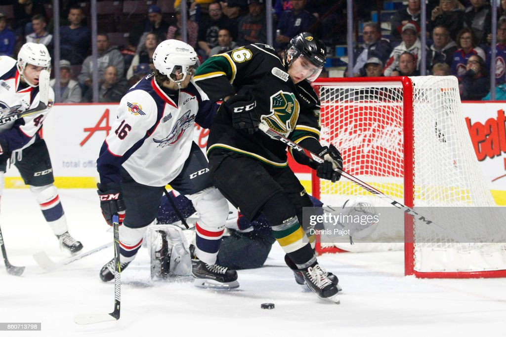 Forward Billy Moskal #76 of the London Knights battles for the puck against forward Chris Playfair #16 of the Windsor Spitfires on October 12, 2017 at the WFCU Centre in Windsor, Ontario, Canada.