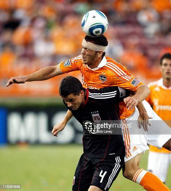 Forward Cam Weaver of the Houston Dynamo goes up for a header over the back of Marc Burch of DC United at Robertson Stadium on April 29 2011 in...