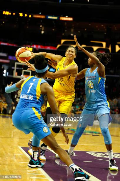 Forward Candace Parker of the Los Angeles Sparks passes the ball as guard Diamond DeShields and center Astou Ndour of the Chicago Sky attempt to...