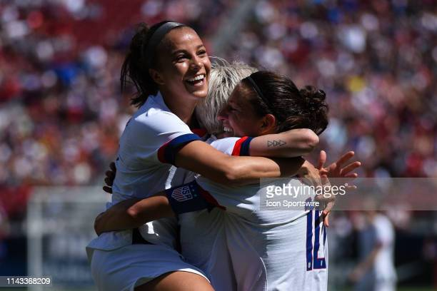 USA forward Carli Lloyd celebrates with teammates including Mallory Pugh left after scoring her side's third goal during the friendly match between...
