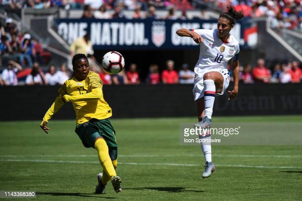 USA forward Carli Lloyd has a shot on goal defended by South Africa defender Bambanani Mbane during the friendly match between the United States...