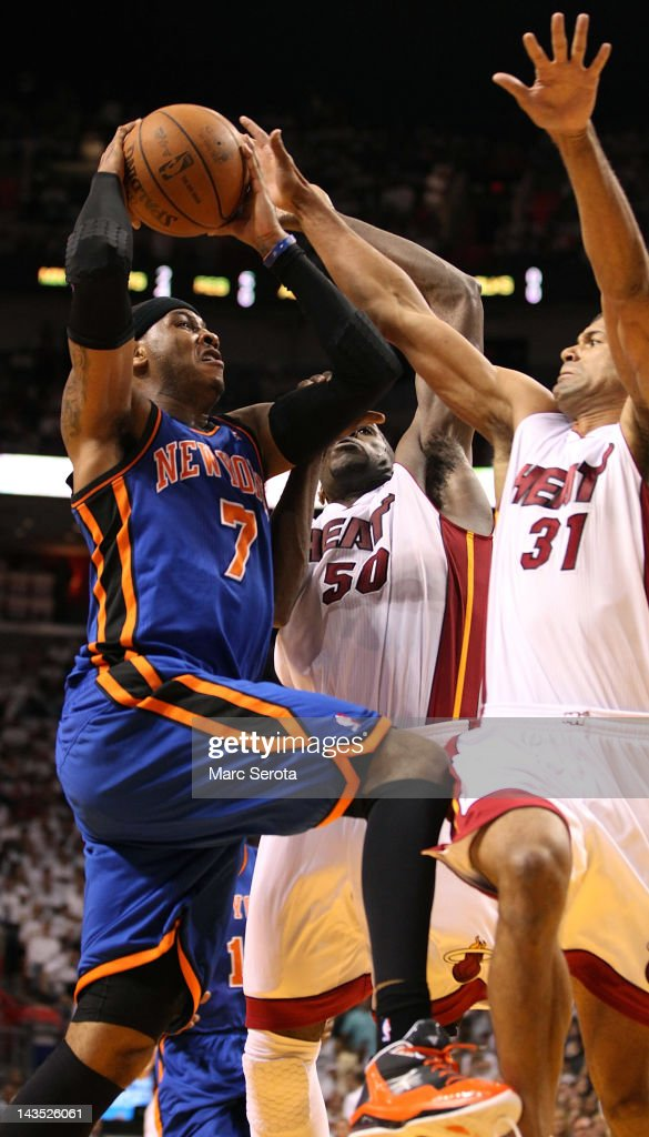 Forward Carmelo Anthony #7 (L) of the New York Knicks is defended by Forward Joel Anthony #50 and Shanes Battier #31 of the Miami Heat in Game One of the Eastern Conference Quarterfinals in the 2012 NBA Playoffs on April 28, 2012 at the American Airines Arena in Miami, Florida.
