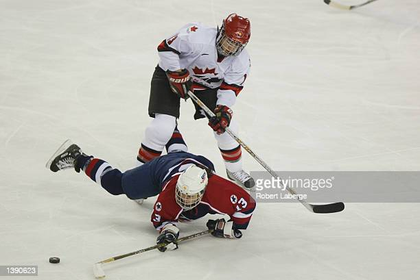 Forward Caroline Ouellette of Canada knocks down forward Julie Chu of the USA as she tries to play the puck during the womens ice hockey gold medal...