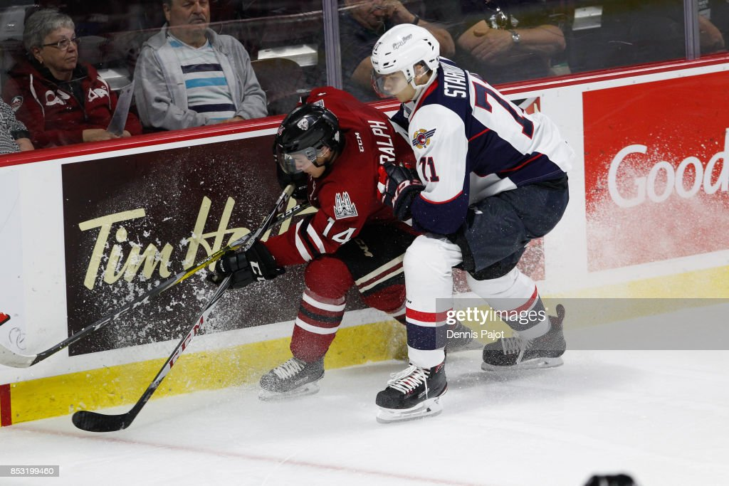 Forward Cedric Ralph #14 of the Guelph Storm moves the puck against defenceman Lev Starikov #71 of the Windsor Spitfires on September 24, 2017 at the WFCU Centre in Windsor, Ontario, Canada.