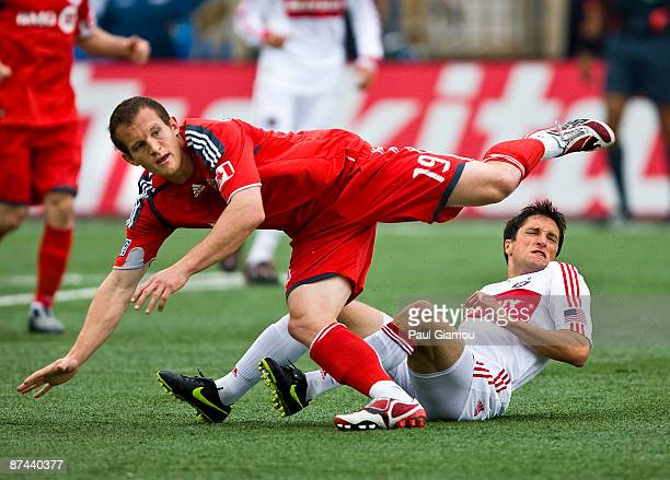 Forward Chad Barrett of Toronto FC trips over midfielder John Thorrington of the Chicago Fire during the match at BMO Field on May 16 2009 in Toronto...